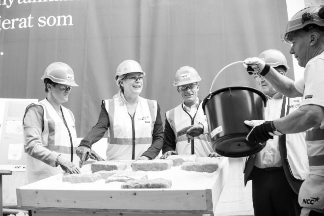 Infrastrukturminister Catharina Elmsäter-Svärd, Torbjörn Rosdahl, exploateringsnämndens ordförande i Stockholms stad Joakim Larsson och NCC:s Carola Lavén lägger de första stenarna i vad som ska bli en konstinstallation.